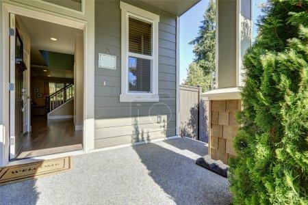 Photo pour Porche d'entrée de la maison grise américaine avec porte ouverte avec tapis d'accueil par une journée ensoleillée. Nord-Ouest, é.-u. - image libre de droit