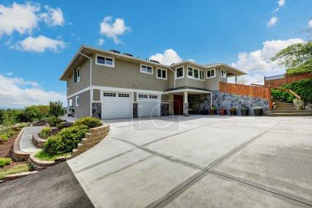 Photo pour Maison de luxe extérieure avec design en pierre naturelle, garage double portes et large allée en béton. Northwest, États-Unis - image libre de droit