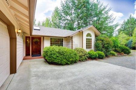 Photo pour Extérieur d'un ranch de chevaux avec portes-fenêtres, allée en béton et buissons verts autour. Northwest, États-Unis - image libre de droit