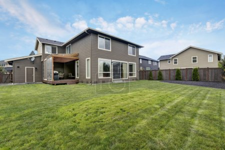 Grass filled back yard. Brown siding house exterior