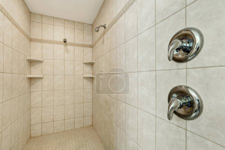 Long walk-in shower with two shower heads .