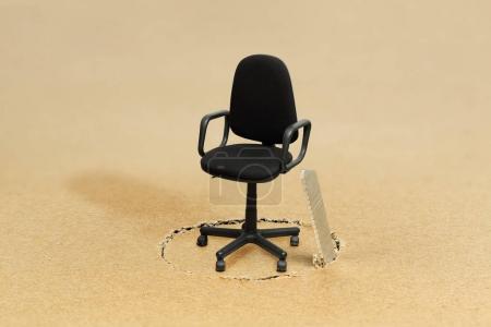 Photo pour Scier le plancher sous un siège de bureau vide, concept pour saper la position de quelqu'un - image libre de droit