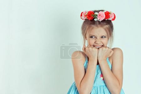 Closeup portrait young little girl biting her finger nails, looking at you with fear of something, anxious, isolated grey background. Human facial expression, body language, reaction, life perception