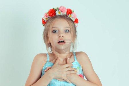 Foto de Retrato asustado niña asustada, niño mirando la cámara conmocionada. Emotion se enfrenta a la expresión del lenguaje corporal inesperada reacción. Modelo de niño caucásico con cabecera floral en fondo verde claro - Imagen libre de derechos