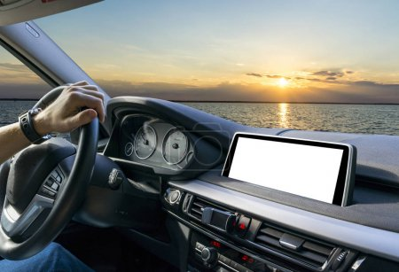Male hands holding car steering wheel. Hands on steering wheel of a car driving near the sea. Man driving a car inside cabin. Multimedia system isolated white blank screen. Copy space