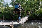 Traveler crossing mountain river on suspension bridge in summer forest