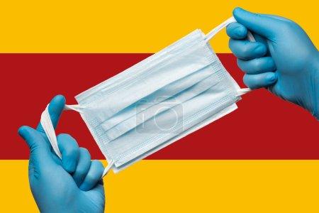 Photo pour Médecin tenant masque respiratoire dans les mains en gants bleus sur le drapeau de fond de l'Espagne. Concept coronavirus quarantaine, grippe, épidémie pandémique. Bandage respiratoire médical pour le visage humain . - image libre de droit