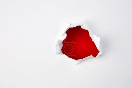 Photo pour Trou rouge dans le papier. Contexte abstrait - image libre de droit