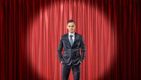 A confident businessman standing in front view in the spotlight with a red stage curtain behind him.