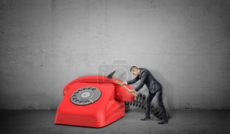 A small businessman fails to destroy a large red retro phone with a broken hammer.