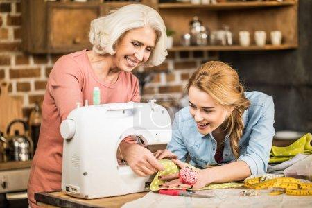 Photo pour Deux femmes souriantes à l'aide de machine à coudre tout en maintenant le tissu brillant - image libre de droit