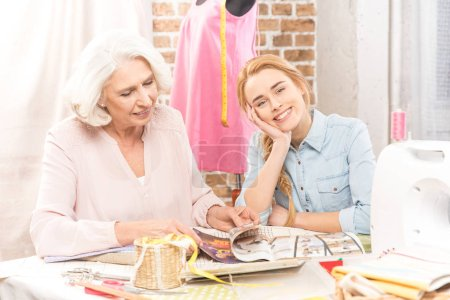 Photo for Two seamstresses sitting at table and choosing model of clothes to sew - Royalty Free Image