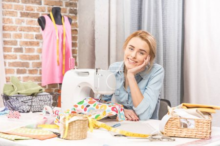 Photo for Smiling teenage girl sitting in front of sewing machine and looking at camera - Royalty Free Image