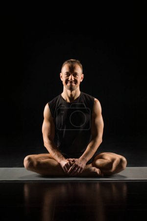 Photo for Young athletic man practicing yoga while sitting in lotus position and smiling at camera isolated on black - Royalty Free Image