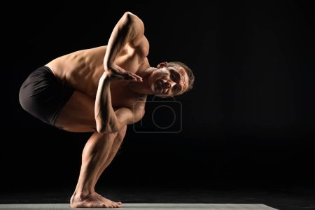 Photo for Athletic man practicing yoga with palms together performing Twisted chair pose and looking at camera isolated on black - Royalty Free Image