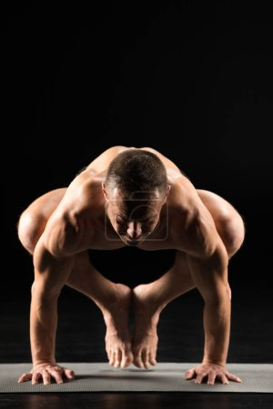 Photo for Young athletic man practicing yoga and doing Kakasana or Crow posture on yoga mat isolated on black - Royalty Free Image