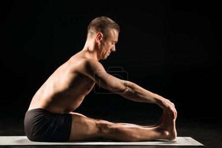 Photo pour Man practicing yoga while sitting with straight legs and holding toes with hands isolated on black - image libre de droit