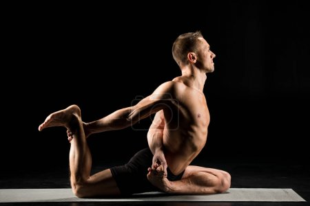 Photo for Young man practicing yoga performing pigeon pose variation on yoga mat isolated on black - Royalty Free Image