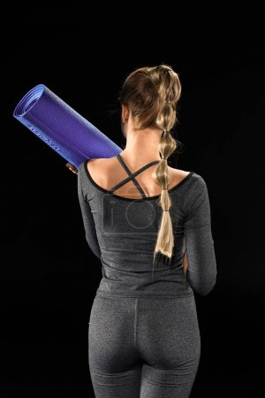 Photo pour Vue arrière de la sportive tenant tapis de yoga sur noir isolé sur noir - image libre de droit