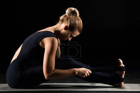 Photo pour Side view of young woman practicing yoga and stretching with yoga strap isolated on black - image libre de droit