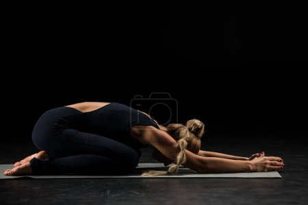 Photo for Woman practicing yoga performing Shashankasana Hare Pose on yoga mat isolated on black - Royalty Free Image