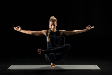 Photo pour Woman practicing yoga performing squat pigeon pose on yoga mat isolated on black - image libre de droit