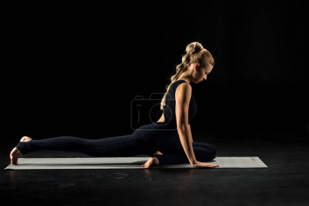 Photo pour Woman practicing yoga sitting in pigeon pose on yoga mat isolated on black - image libre de droit