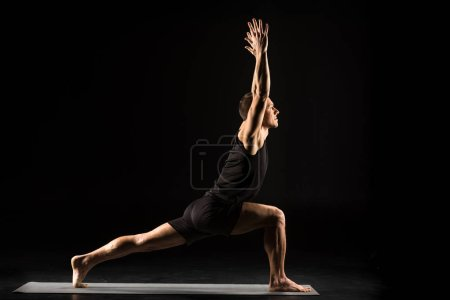 Photo for Man practicing yoga standing in variation of Warrior I posture or Virabhadrasana One pose isolated on black - Royalty Free Image