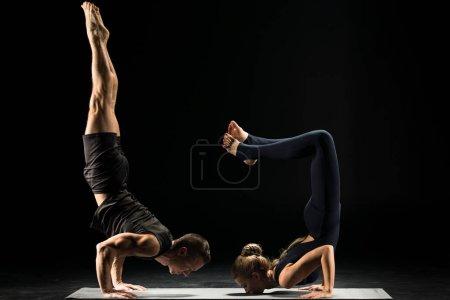 Photo pour Couple effectuant acroyoga faisant handstand Ganda Bherundasana ou Formidable Face Posture isolé sur noir - image libre de droit