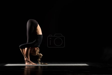 Photo pour Woman performing Uttanasana on yoga mat isolated on black - image libre de droit