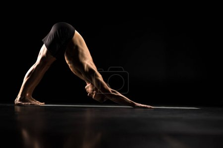 Photo for Man performing Adho Mukha Svanasana or Downward Facing Dog Pose isolated on black - Royalty Free Image