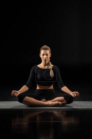 Photo for Young woman performing Sukhasana and meditating on yoga mat isolated on black - Royalty Free Image