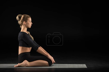 Photo for Young woman performing Vajrasana on yoga mat isolated on black - Royalty Free Image
