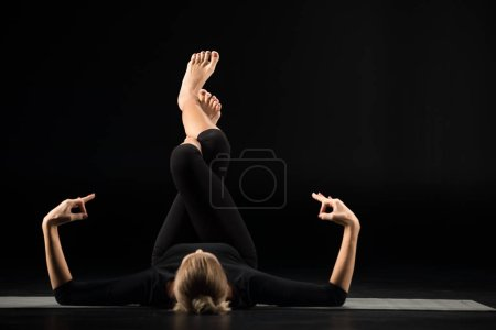 Photo for Woman practicing yoga and meditating while lying on her back isolated on black - Royalty Free Image