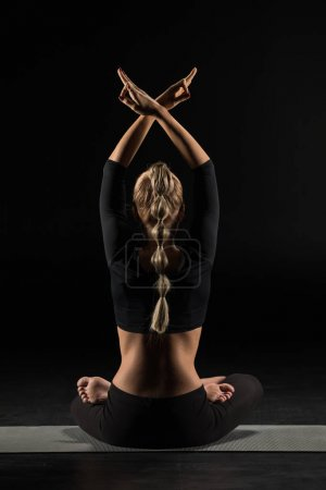 Photo pour Rear view of woman sitting in lotus position and meditating isolated on black - image libre de droit