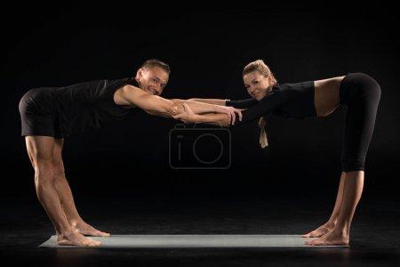 Photo pour Jeune couple s'échauffant en demi-courbure vers l'avant debout - Ardha Uttanasana pose sur tapis de yoga isolé sur noir - image libre de droit