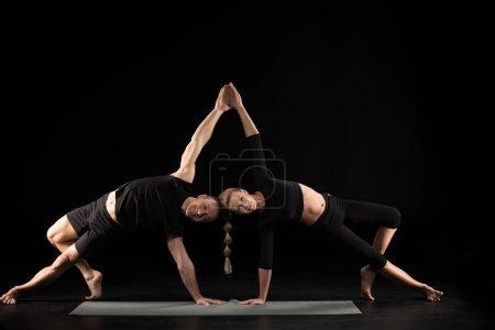 Photo pour Couple effectuant acroyoga pose de planche latérale sur tapis de yoga isolé sur noir - image libre de droit