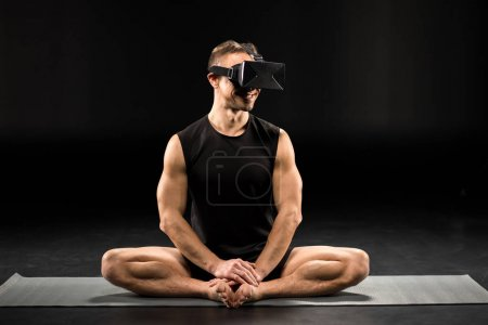 Photo for Man in virtual reality glasses sitting in Bound Angle pose and smiling on yoga mat isolated on black - Royalty Free Image