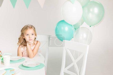 Adorable girl at birthday table