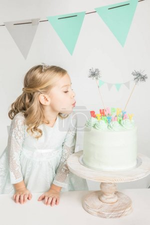Girl blowing at birthday cake