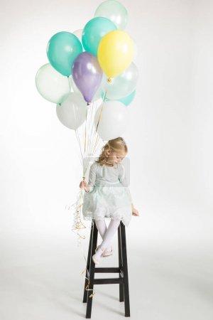 Photo pour Petite fille mignonne assise sur une chaise de bar avec des ballons à air isolé sur blanc - image libre de droit