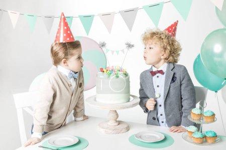 Photo pour Deux petits garçons dans des chapeaux de cône soufflant des bougies sur le gâteau d'anniversaire isolé sur blanc - image libre de droit