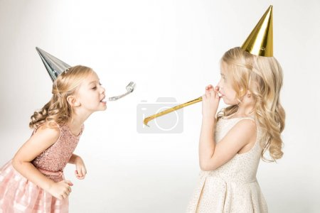 Photo pour Two little girls in cone hats having fun with party blowers isolated on white - image libre de droit