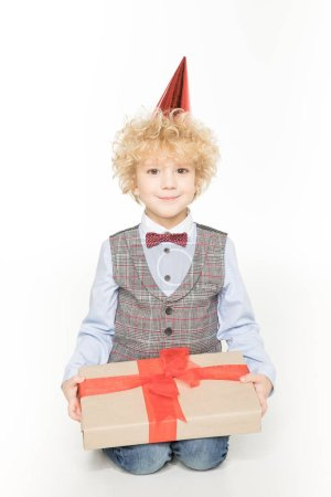 Photo for Stylish little boy in cone hat holding birthday present and smiling  isolated on white - Royalty Free Image