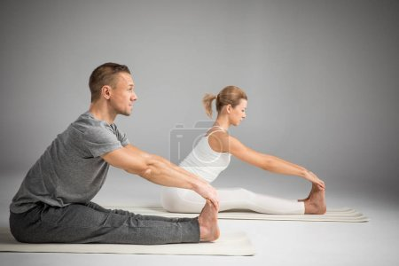 Photo pour Couple practicing yoga sitting in Paschimottanasana (Seated Forward Bend) yoga position isolated on grey - image libre de droit