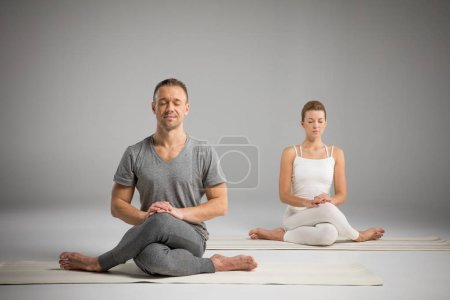 Photo pour Young athletic man and woman sitting in Gomukhasana, Cow face pose on yoga mats isolated on grey - image libre de droit
