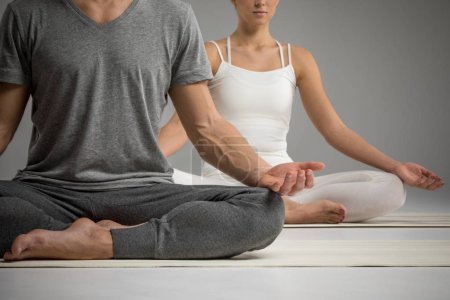 Photo pour Young couple practicing yoga sitting in lotus position on yoga mats  isolated on grey - image libre de droit