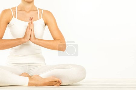 Photo pour Woman sitting in lotus position with Namaste Mudra gesture  isolated on white - image libre de droit