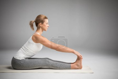 Foto de Woman practicing yoga sitting in Paschimottanasana (Seated Forward Bend) yoga pose   isolated on grey - Imagen libre de derechos
