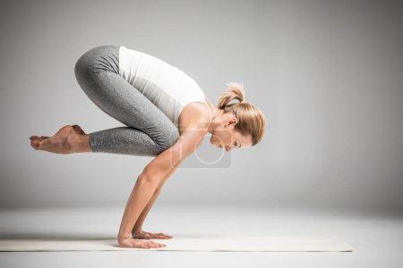 Photo for Woman practicing yoga standing in Bakasana or Crane position  isolated on grey - Royalty Free Image